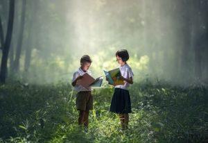 Deux bénéficiaires d'Enfants d'Aise lisant un livre dans une forêt féérique.