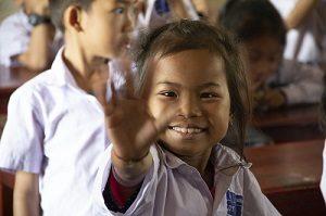 Une enfant souriante tendant la main ouverte d'Enfants d'Asie